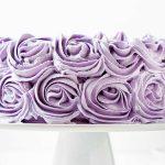 Ube cake with purple ube halaya frosting rosettes on white cake stand