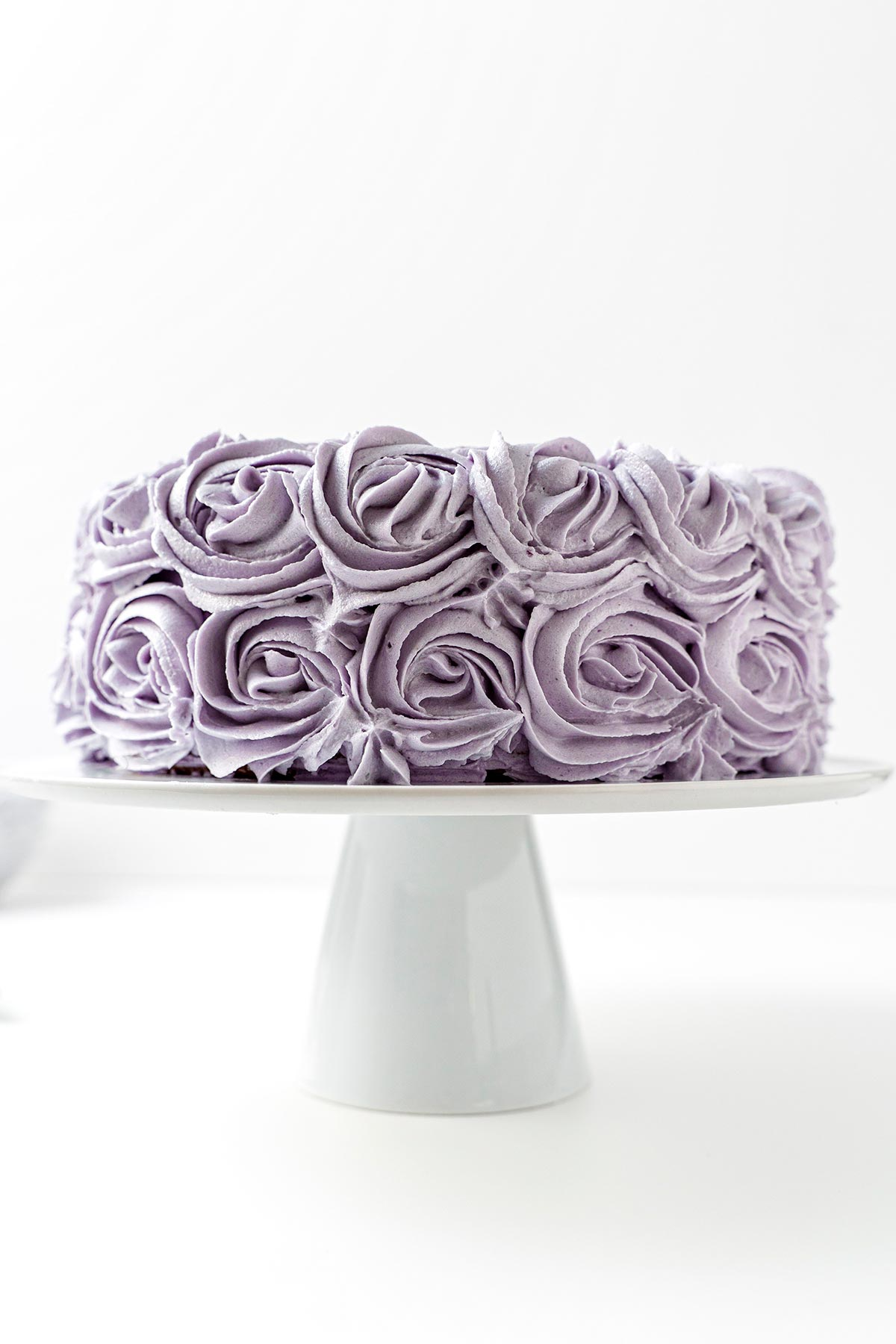 Ube Halaya Cake with purple frosting roses on white cake stand