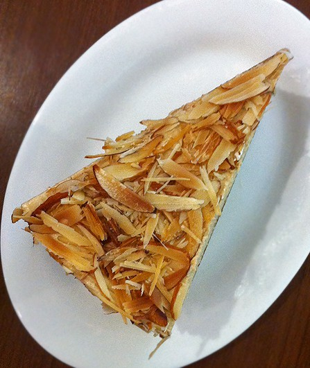 A plated slice of coffee cake with toasted almond slices