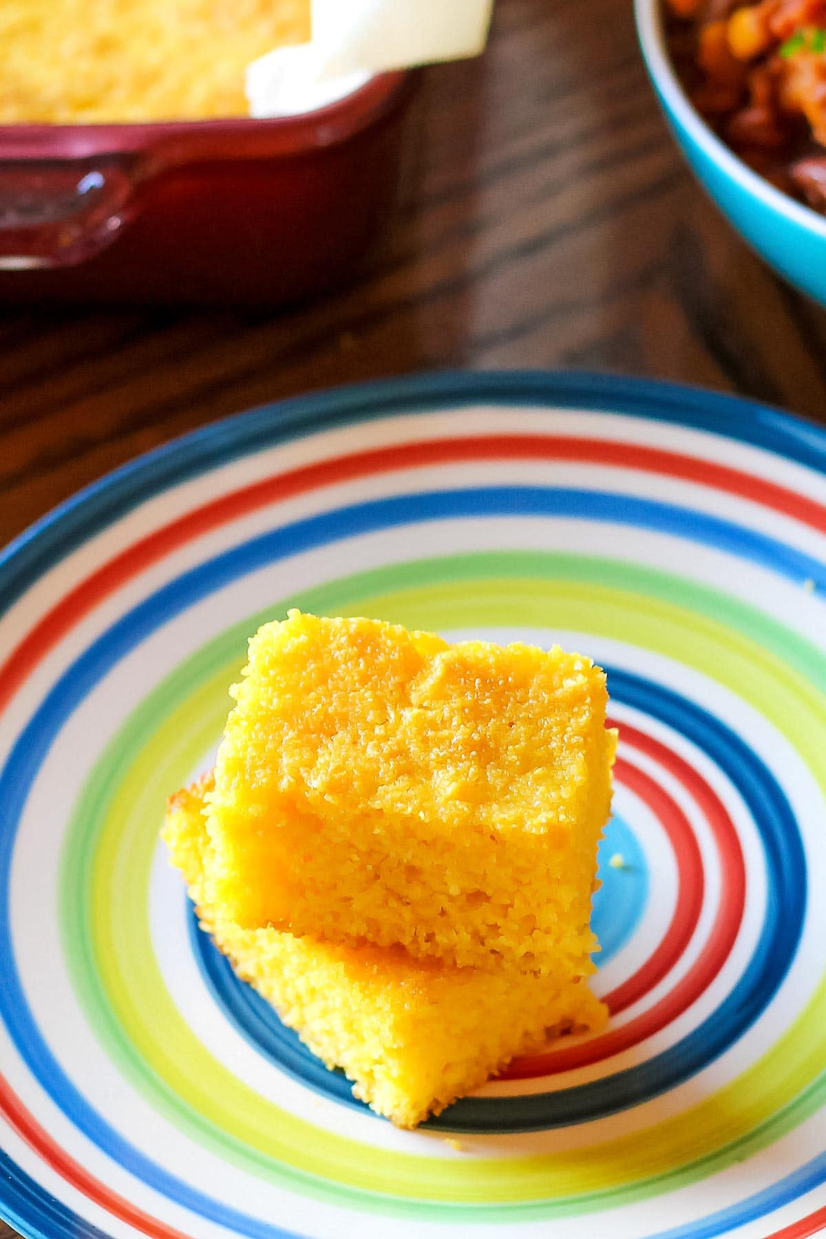 Pieces of dairy free cornbread, with baking pan and bowl of chili in background