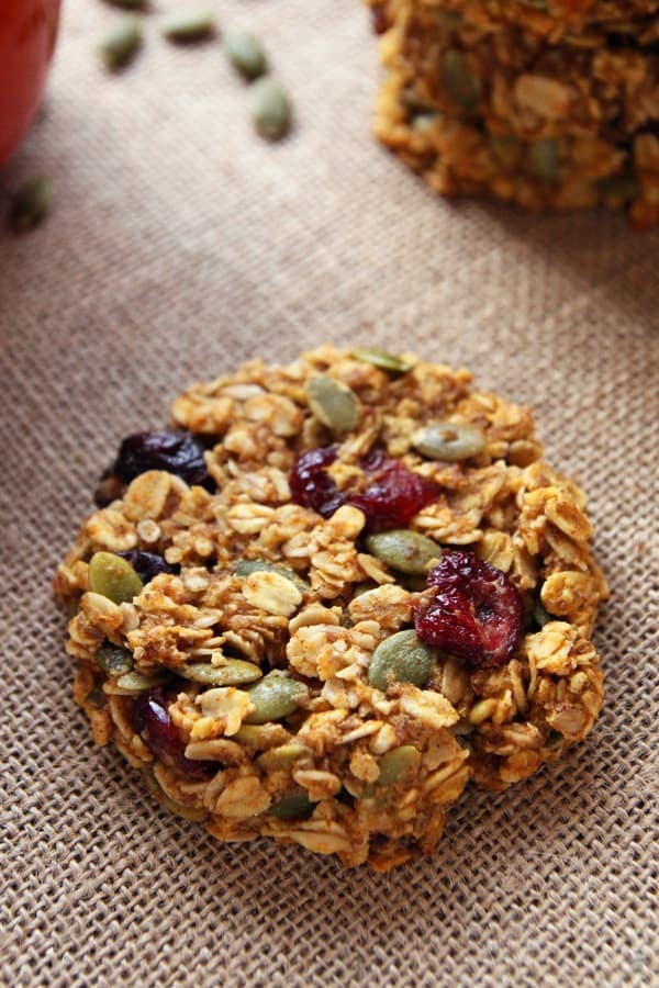 These healthy pumpkin breakfast cookies make a nutritious and portable breakfast that tastes like fall! This gluten-free + clean eating breakfast treat is made with wholegrain oats, cranberries, pumpkin seeds + honey