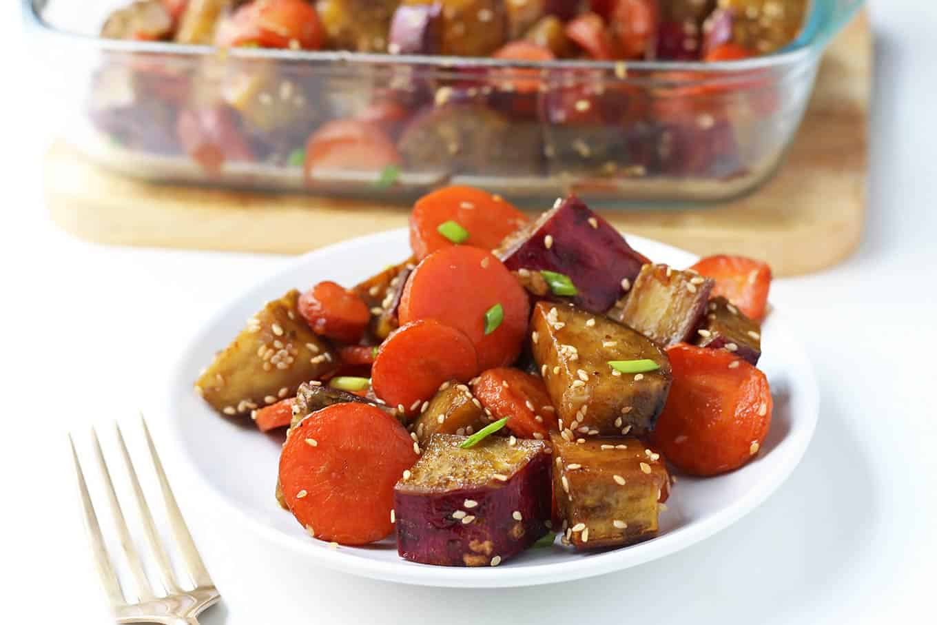 Oven roasted sweet potatoes and carrots with a honey sesame glaze make a delicious healthy vegetable side dish for the holidays or any time of year.