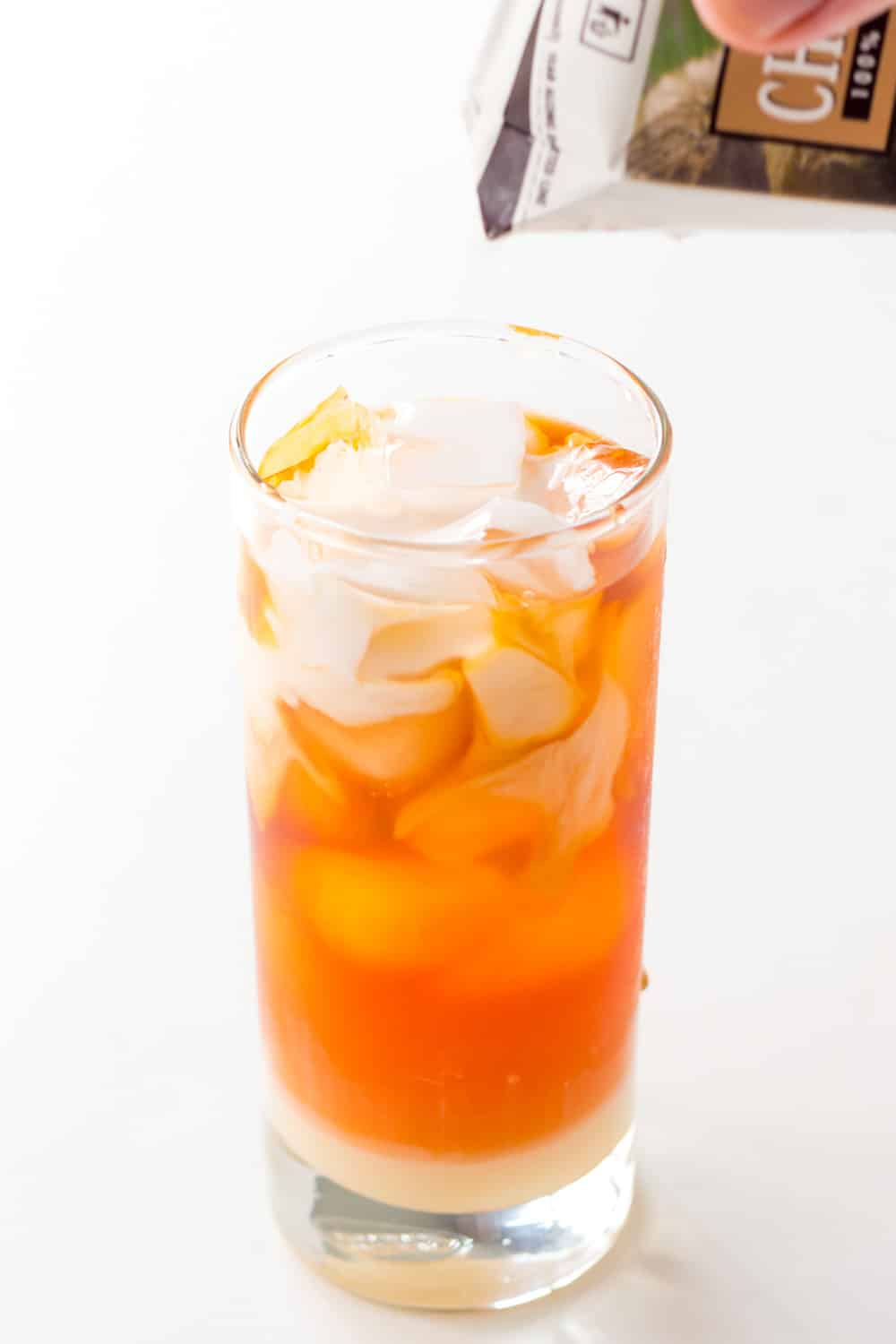 This refreshing Thai Iced Tea with Milk is perfect to accompany a spicy Thai food dinner. This homemade recipe uses palm sugar and coconut milk in place of evaporated and sweetened condensed milk to make it dairy free and vegan.