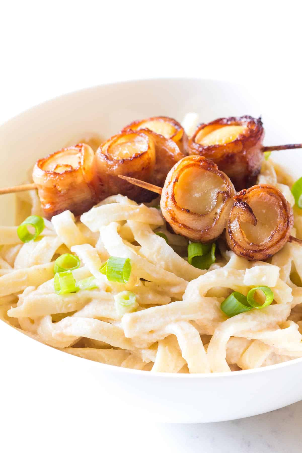 Bacon Wrapped Scallops on skewer on top of pasta in bowl
