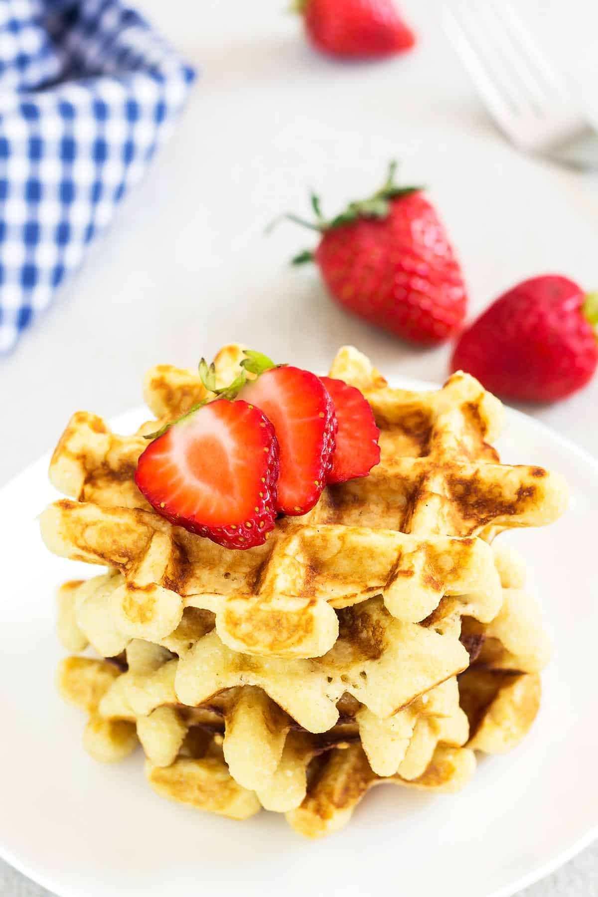 Stack of 3 coconut flour waffles with strawberries on a plate