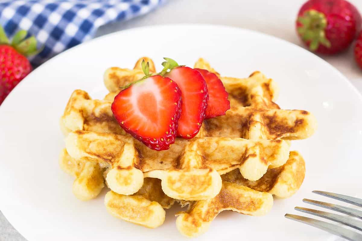 Two gluten free waffles on a plate with strawberries