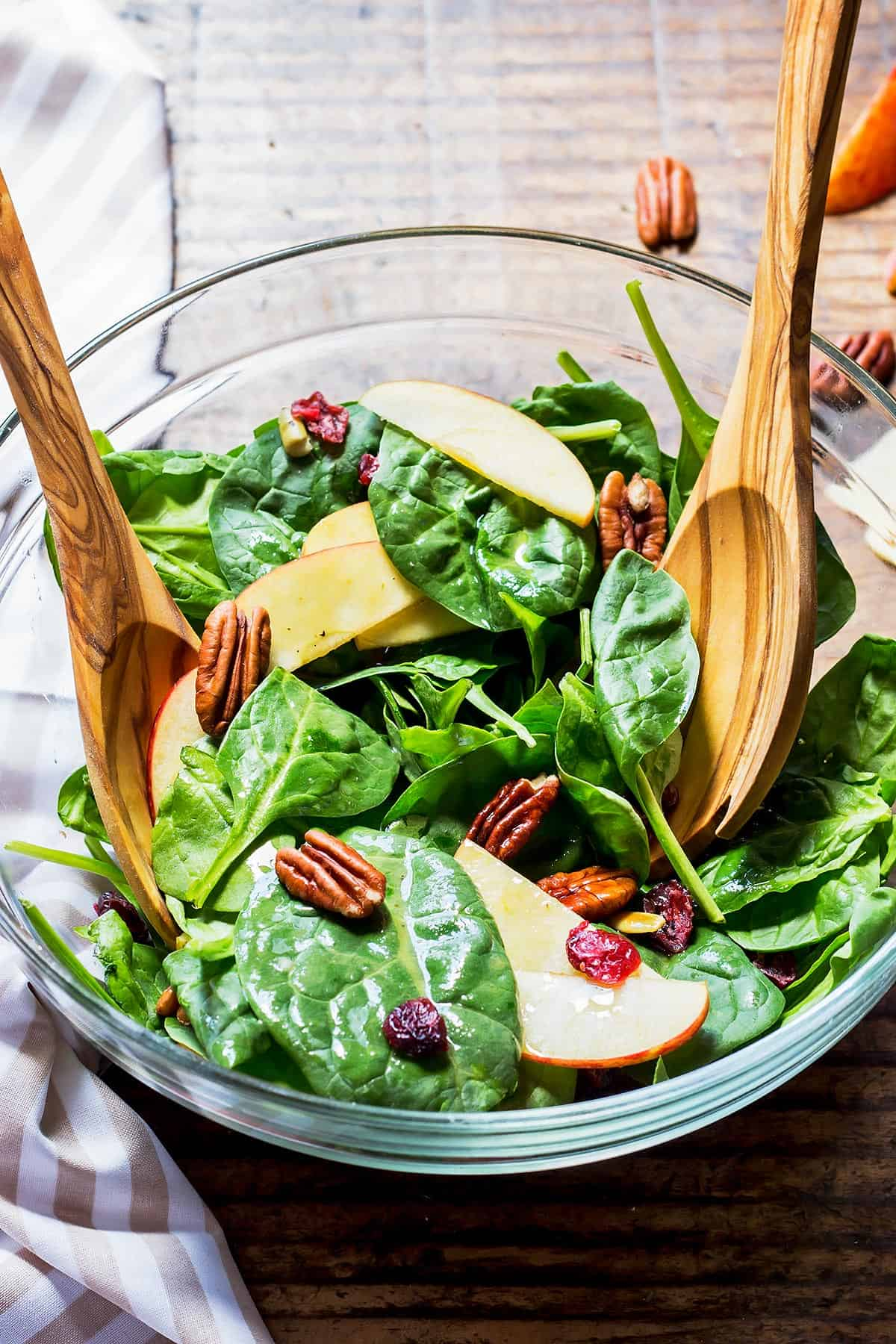 Harvest Spinach Salad in glass bowl with olive wood utensils