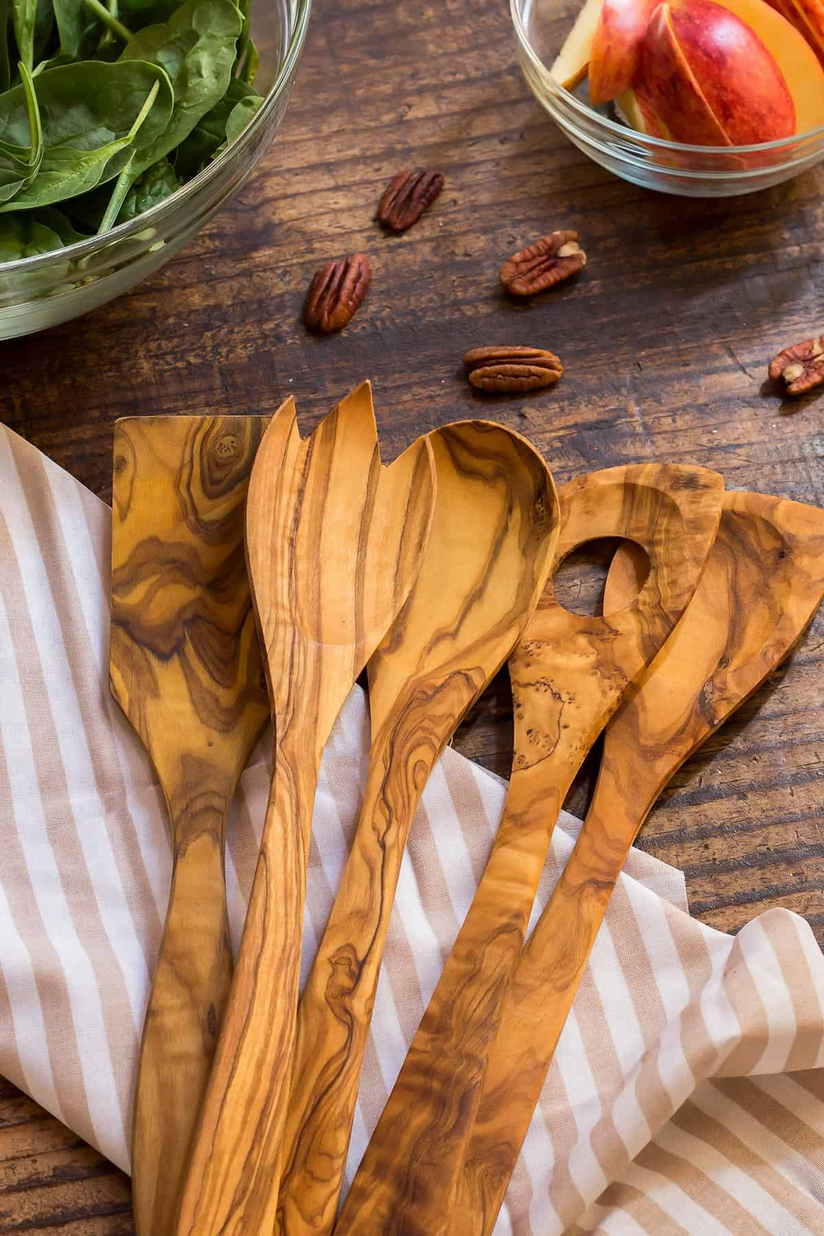 5 Olive Wood Cooking Utensils fanned out on a table