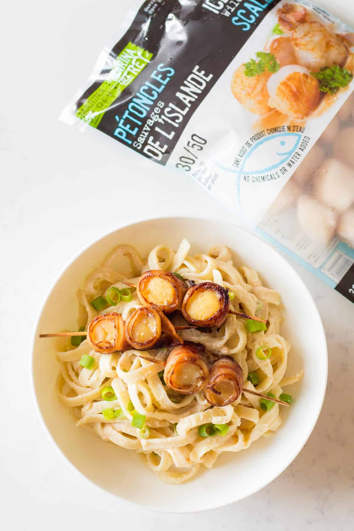 Bacon Scallop Pasta in white bowl, bag of frozen seafood on side