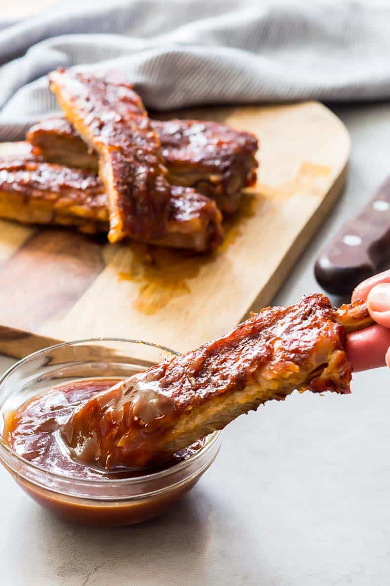 Instant Pot Rib Bone being dipped in BBQ sauce