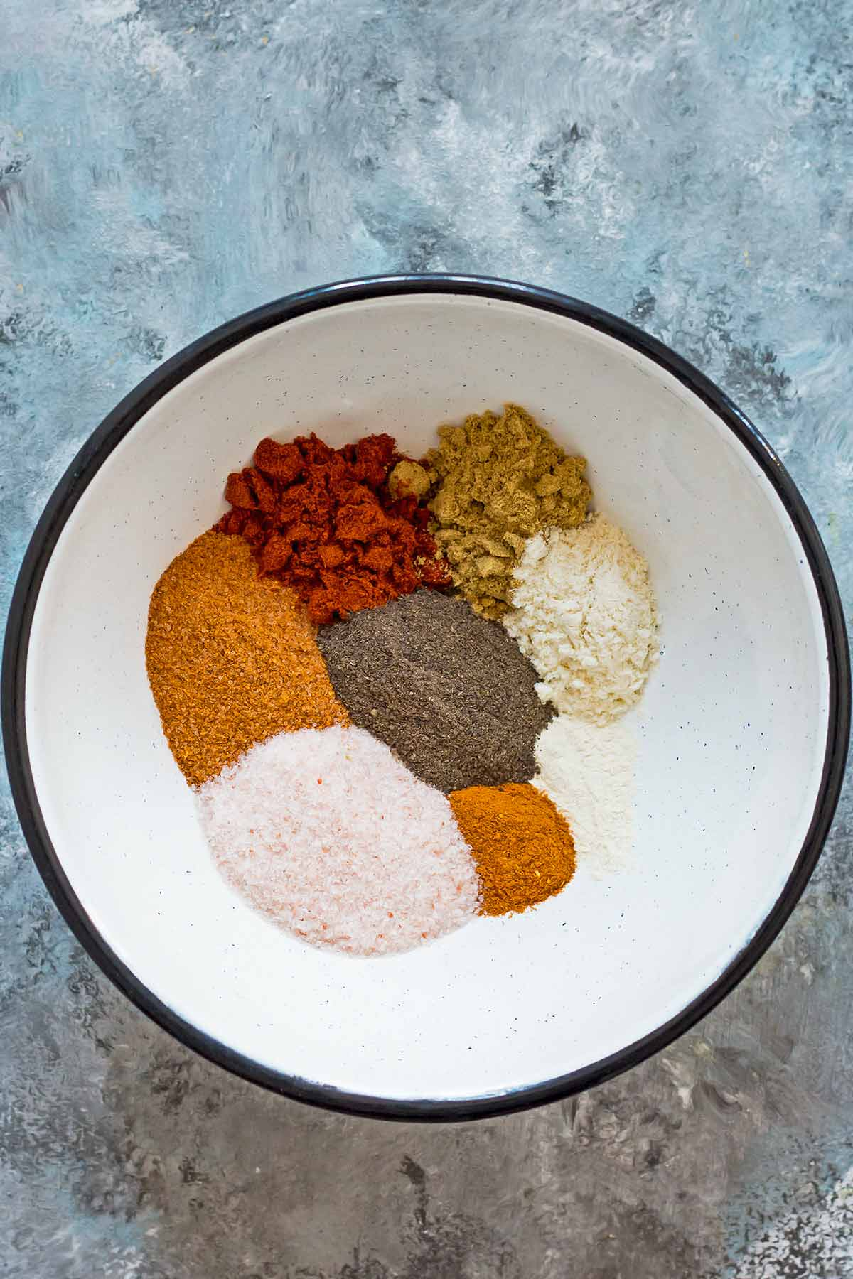 Bowl of individual spices for chili seasoning before mixing