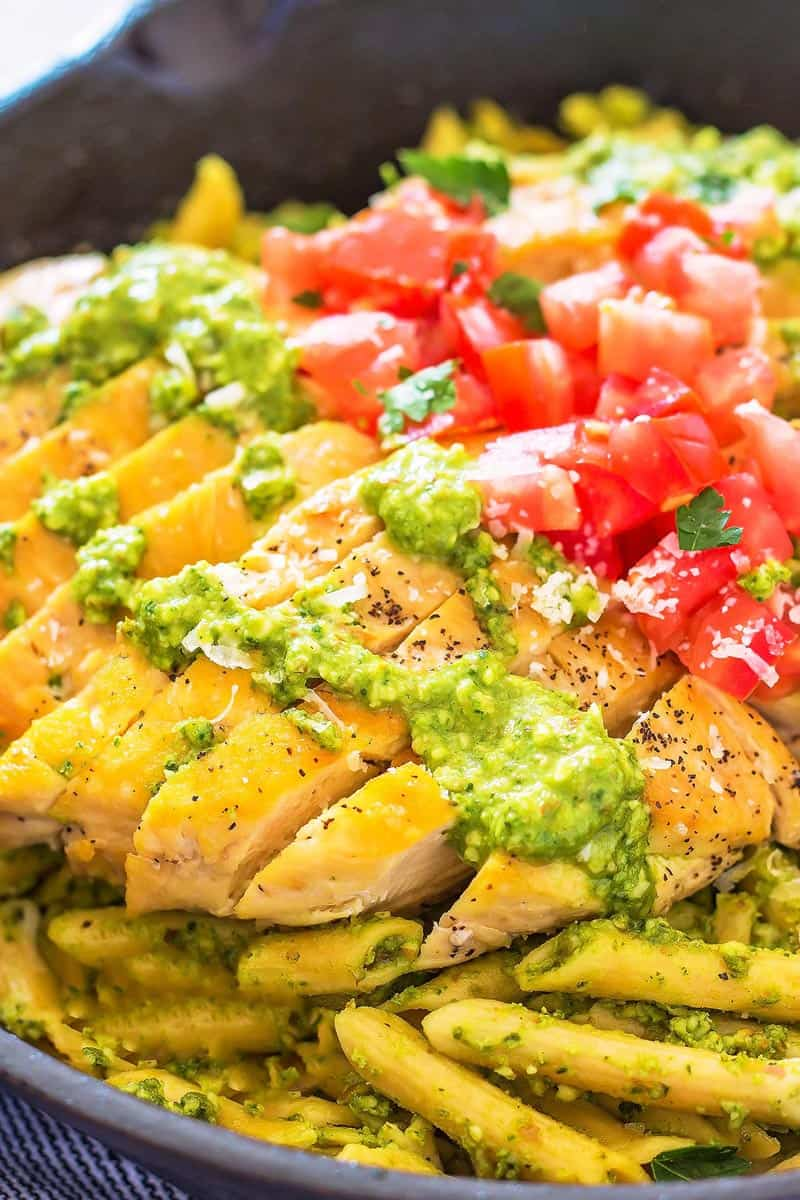 Close up of sliced chicken on pesto pasta in a skillet