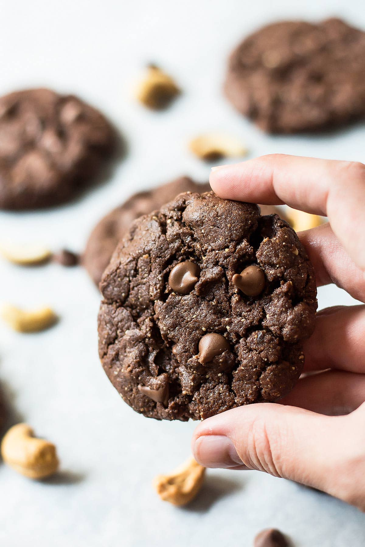 Hand holding flourless chocolate cookie