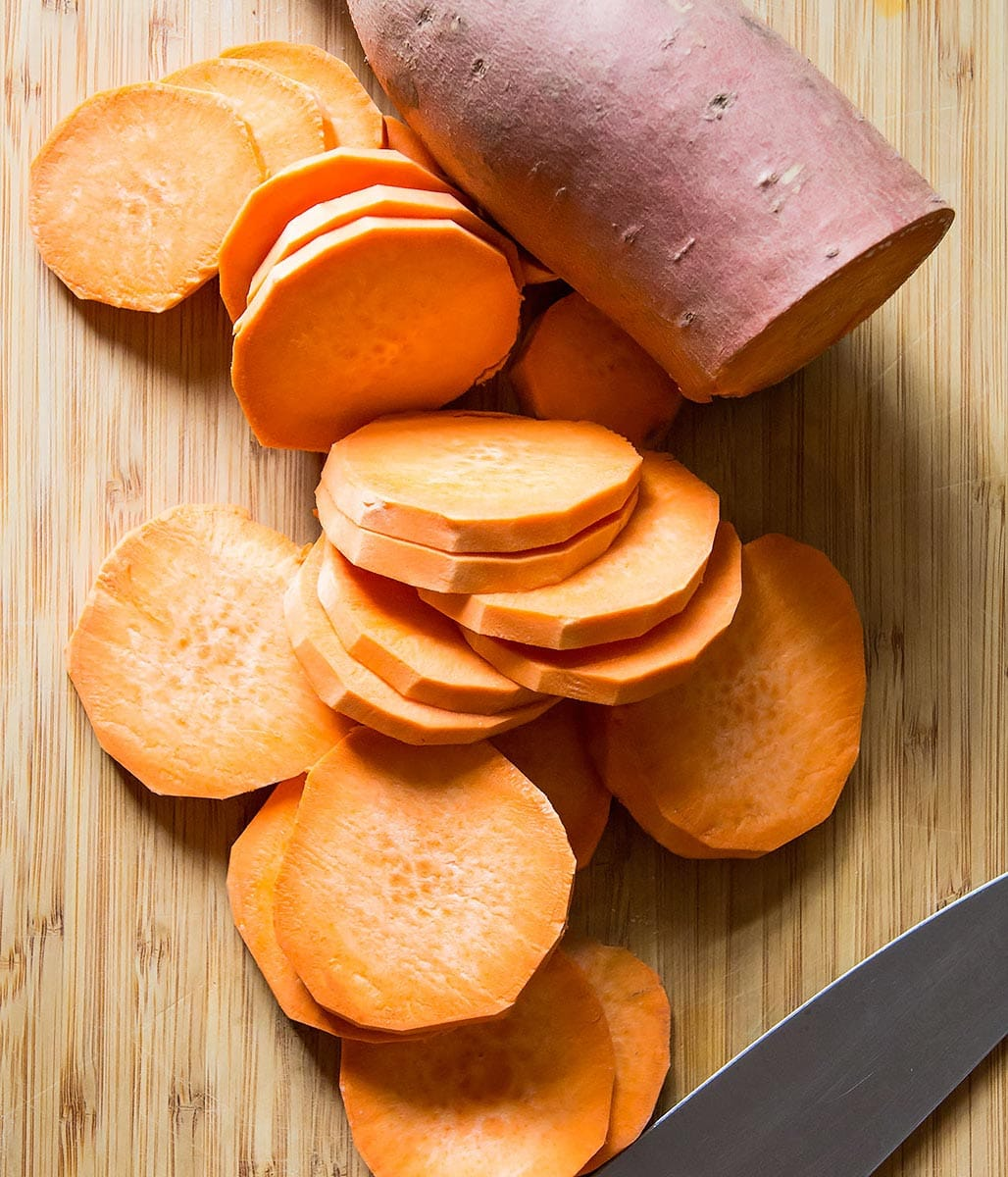 Sliced sweet potato rounds on cutting board
