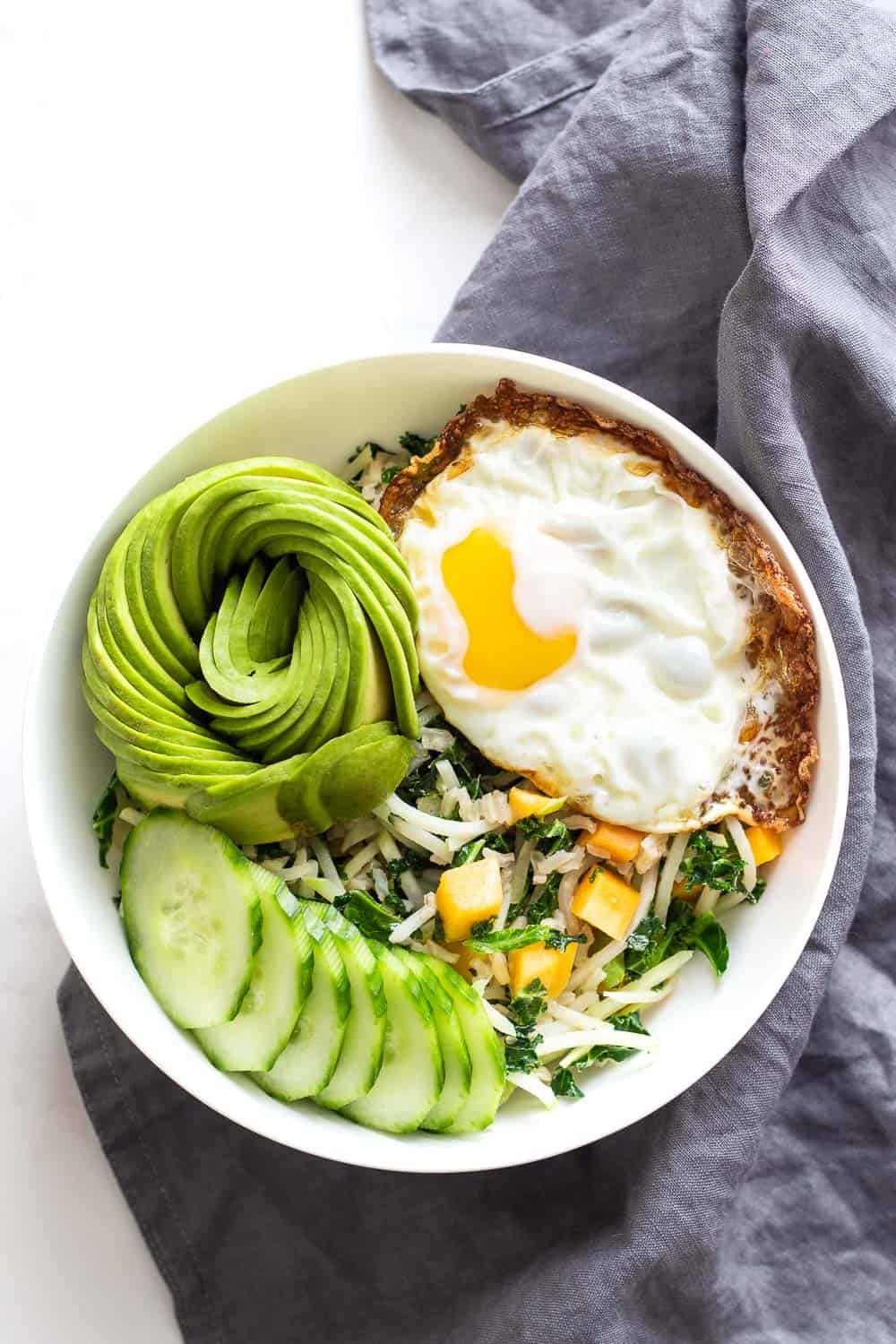 Thai Breakfast Bowl with kale, fried egg, avocado, cucumber