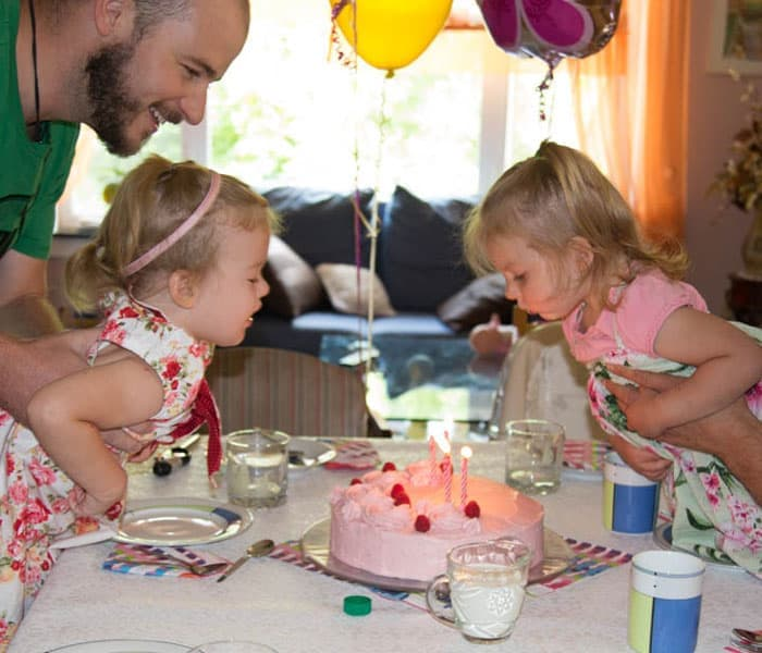 Two girls blowing out birthday cake candles