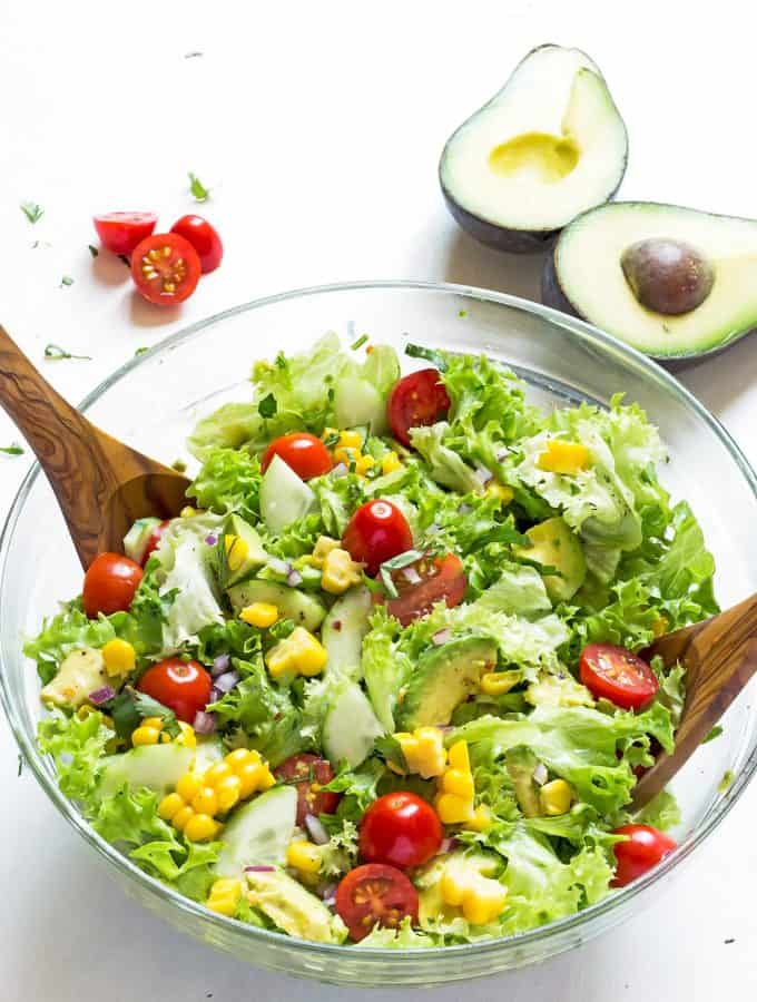 Corn Tomato Avocado Salad in a glass bowl with serving spoons