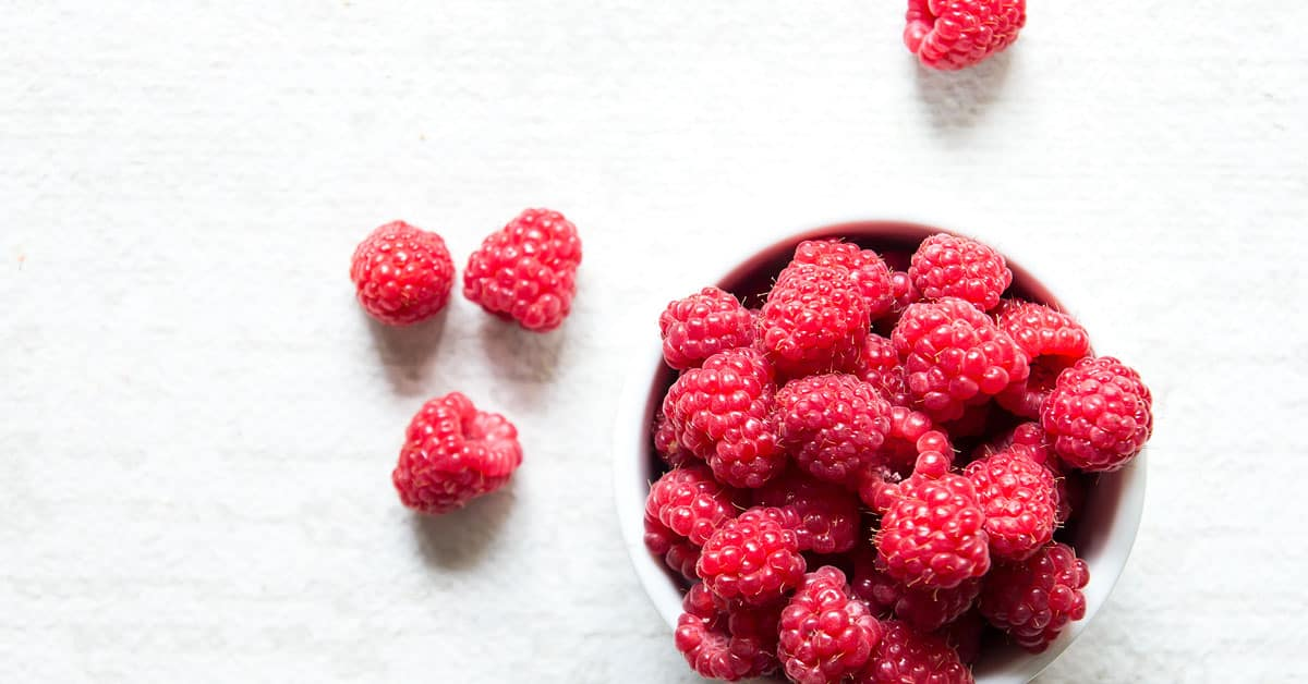 raspberries in a bowl and on table