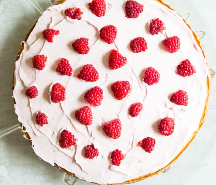 Raspberry cake filling on cake layer with fresh raspberries