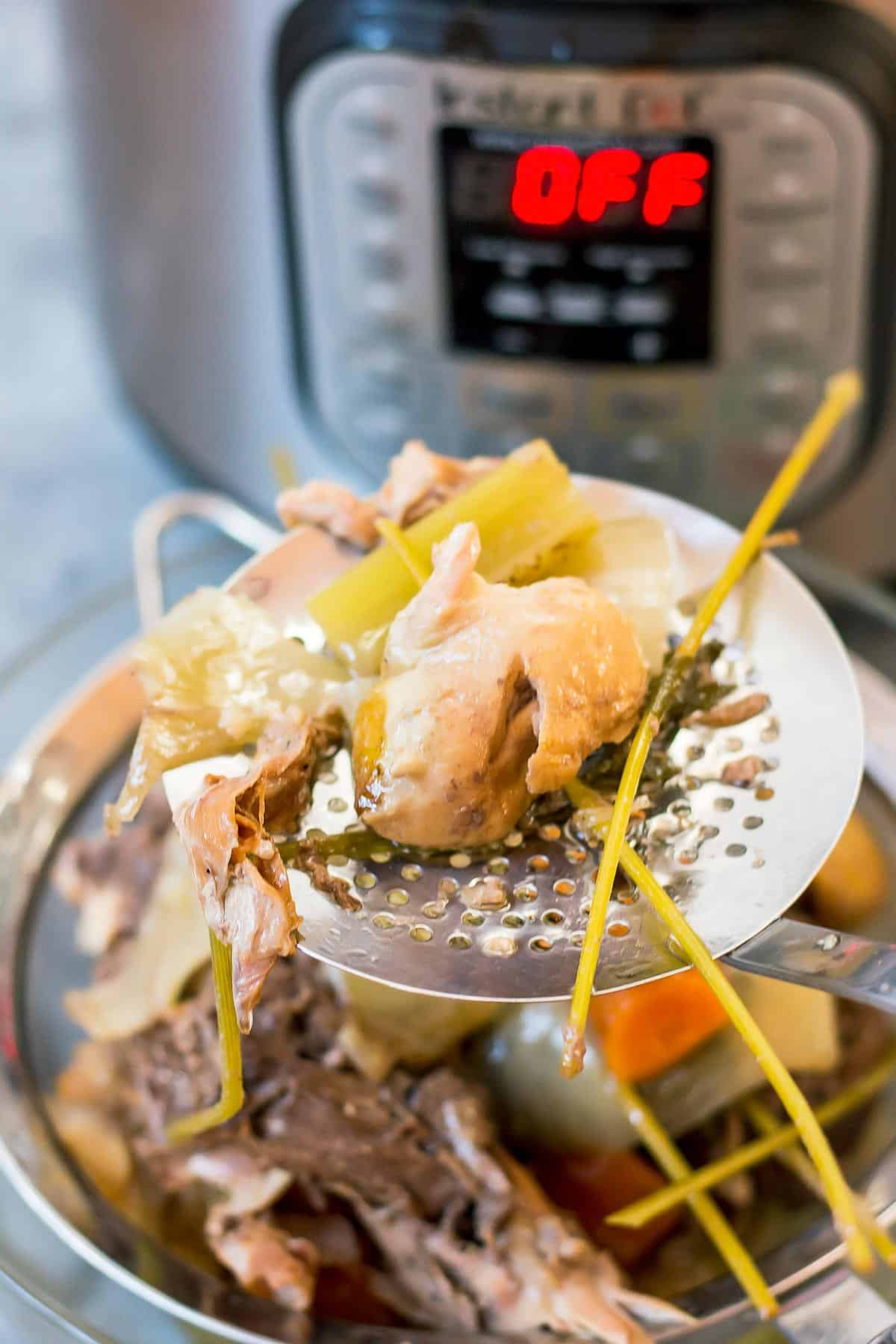 Slotted Spoon Holding Bone Broth Scraps