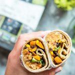 Hand holding two vegan burrito halves