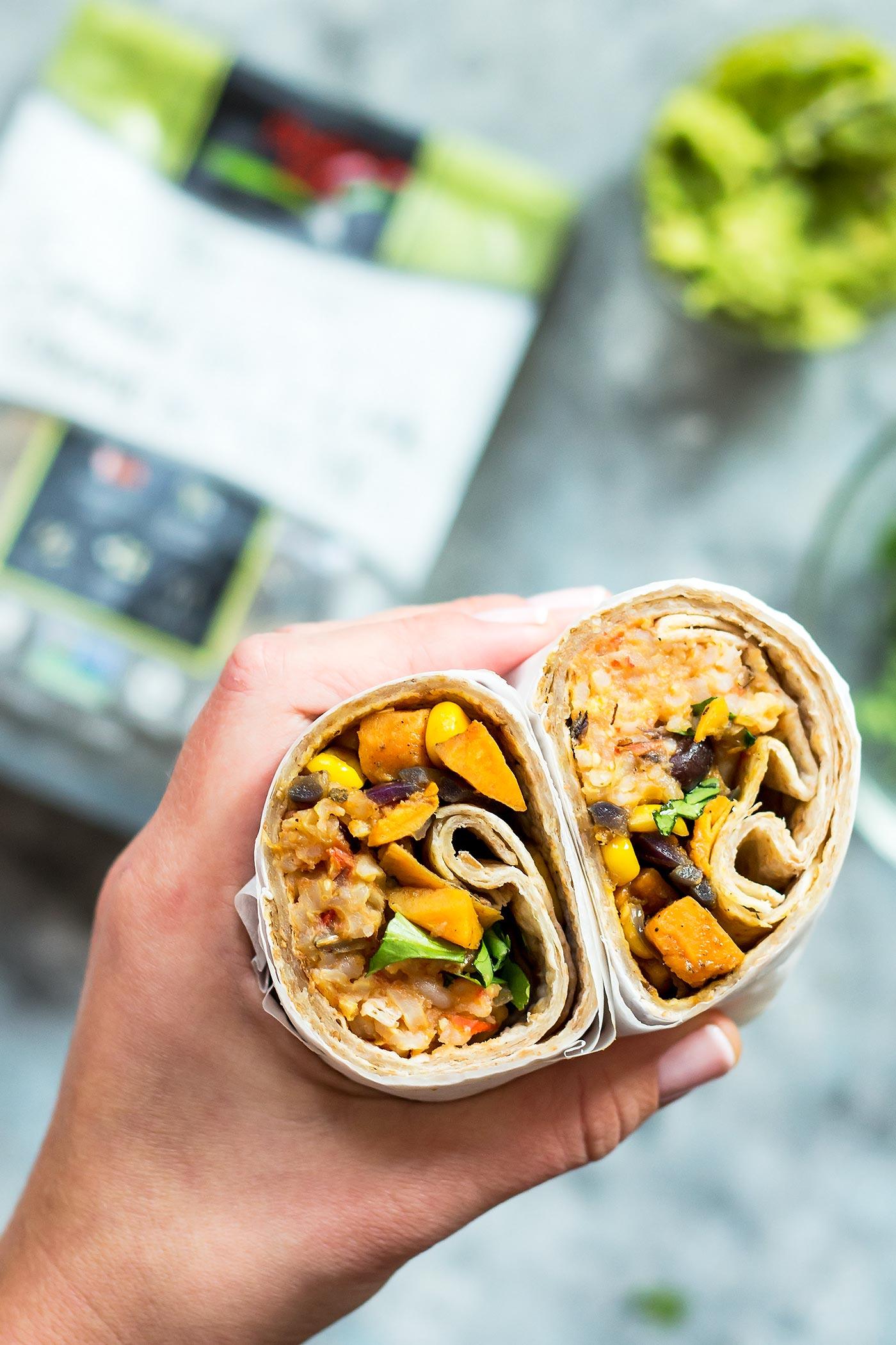 Holding two vegan burrito halves