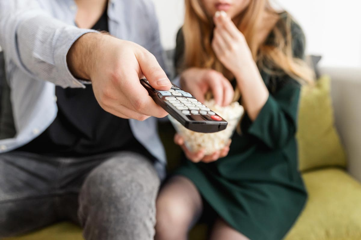 Couple Eating Popcorn Holding Remote