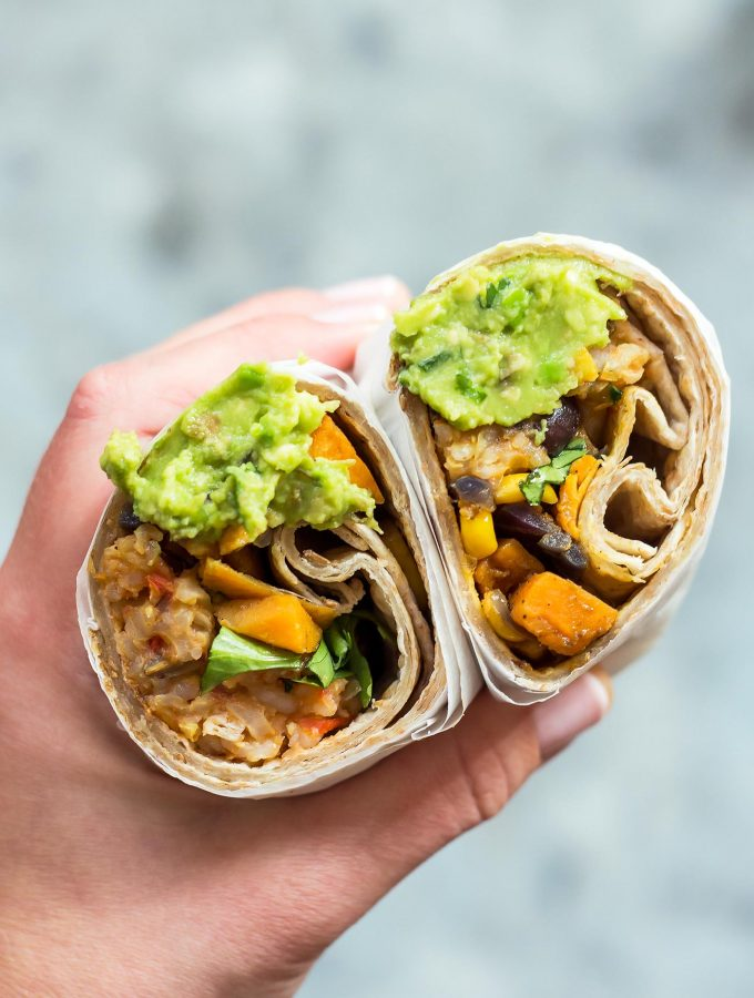 Vegan burrito with guacamole in hand