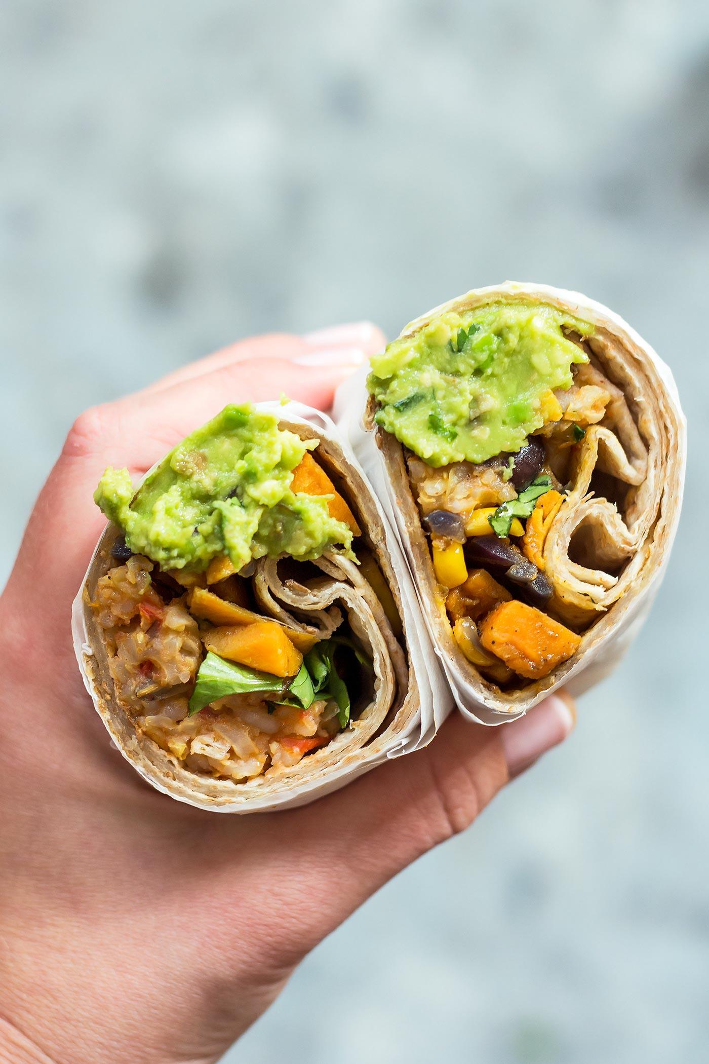 Vegan burrito with guacamole in hand