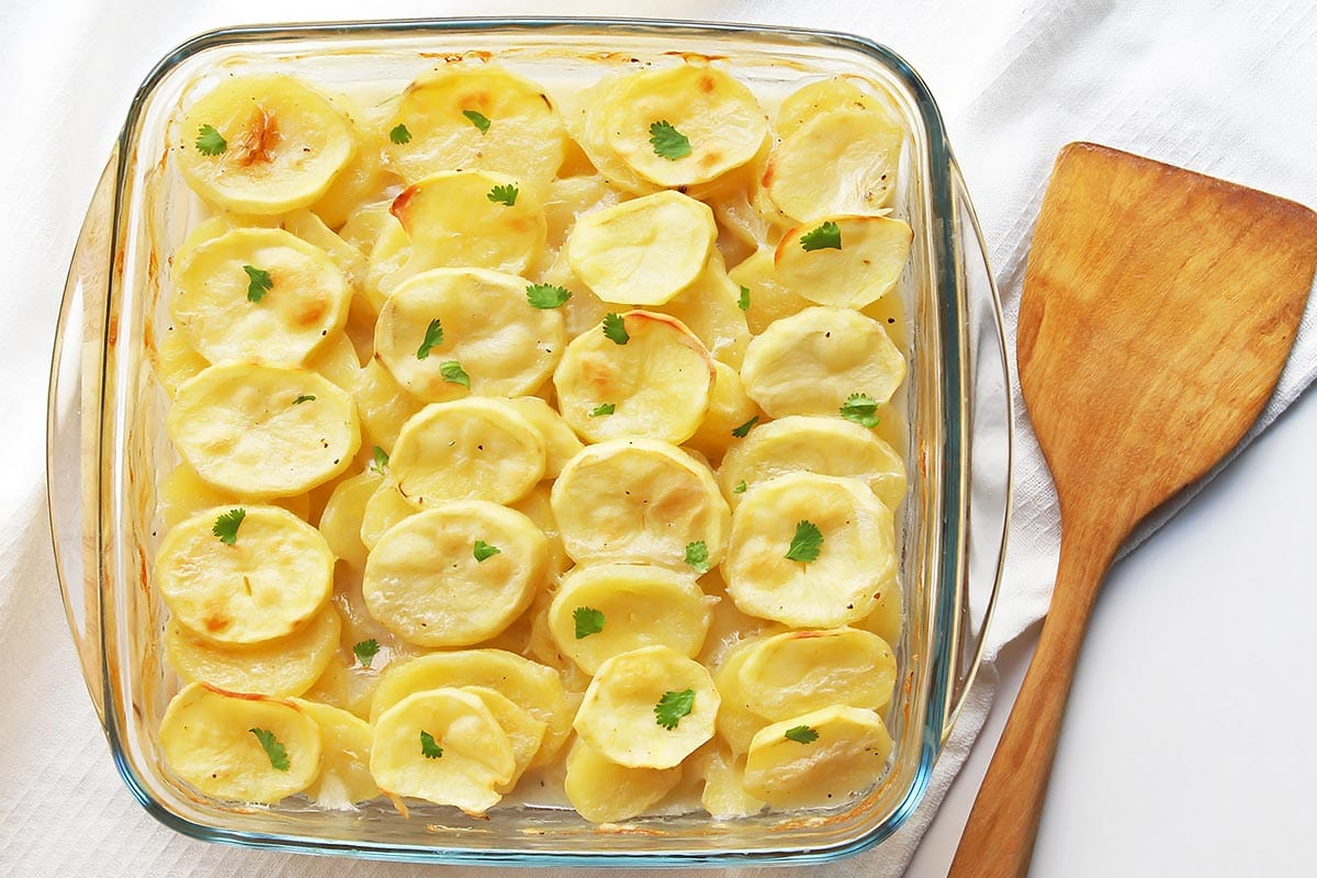Vegan Scalloped Potatoes in Baking dish with wooden spatula on side