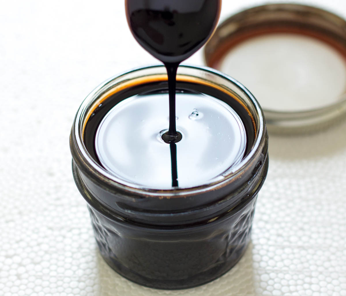 Spoon in a jar of balsamic reduction sauce