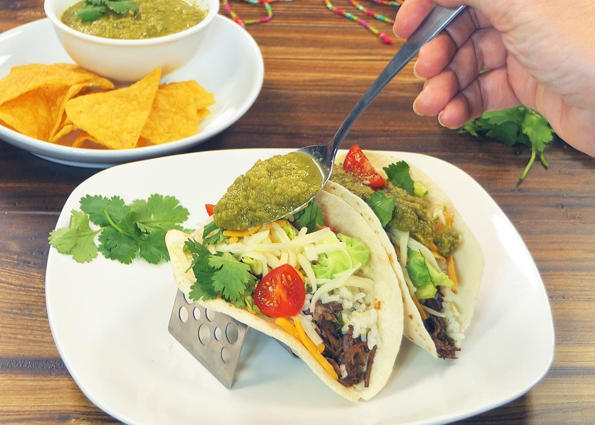 Spooning Salsa Verde on Tacos