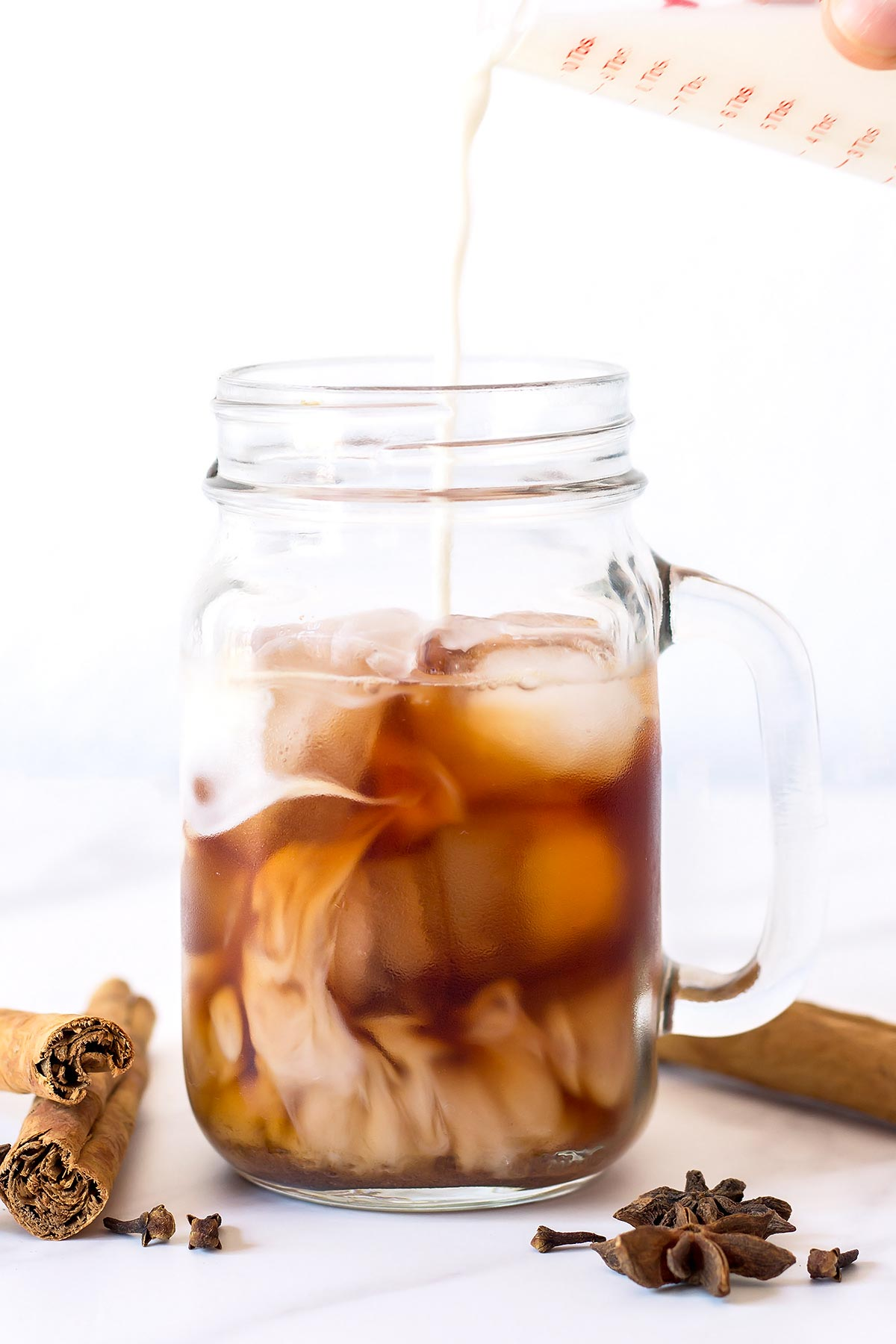 Milk pouring into Iced Chai Tea