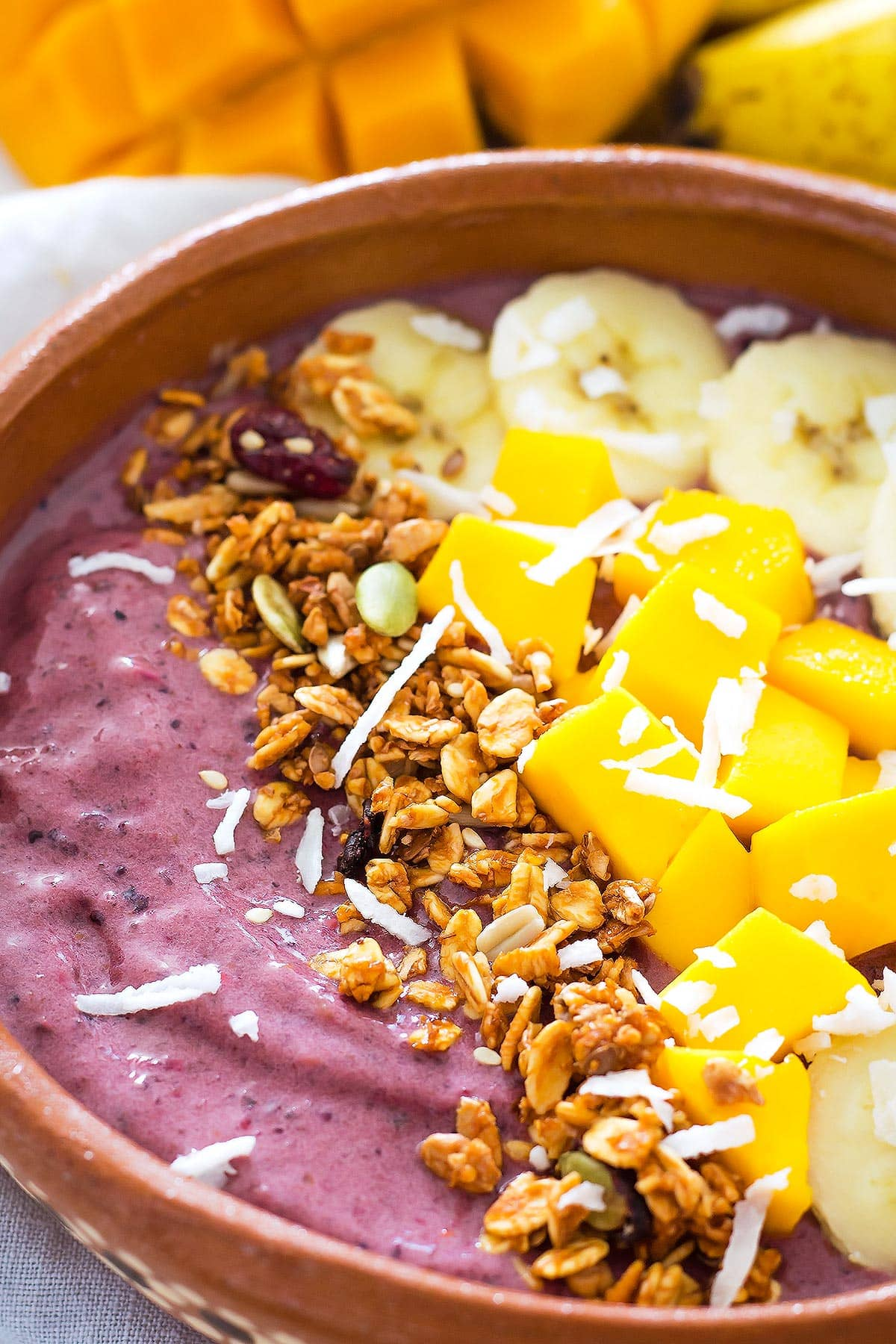 Purple Acai Berry Smoothie in a bowl with banana, mango, granola, coconut topping
