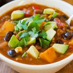 Bowl of Vegan Lentil Chili topped with avocado and cilantro