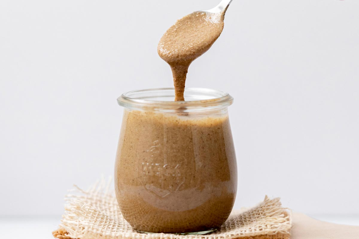 Small jar of homemade tahini with spoon