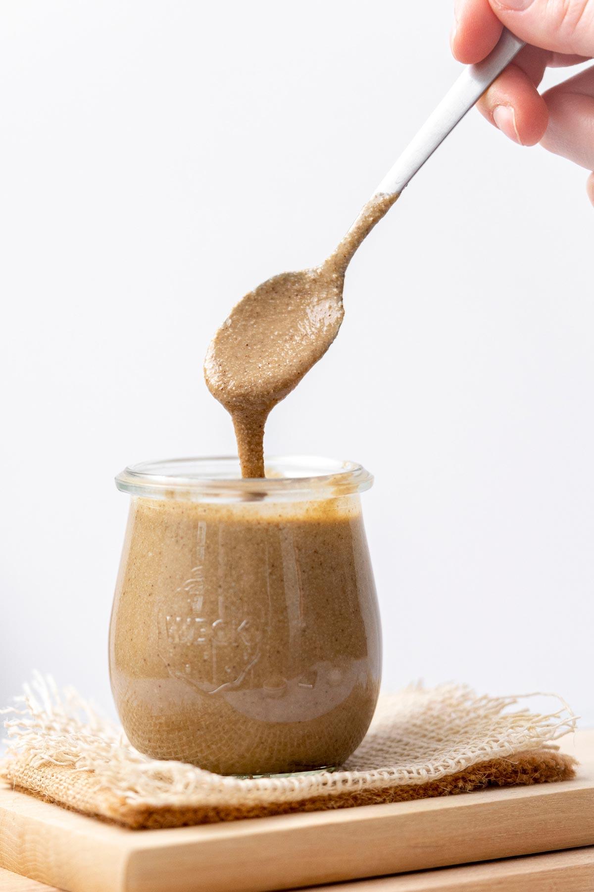 Spoon drizzling homemade tahini into small jar