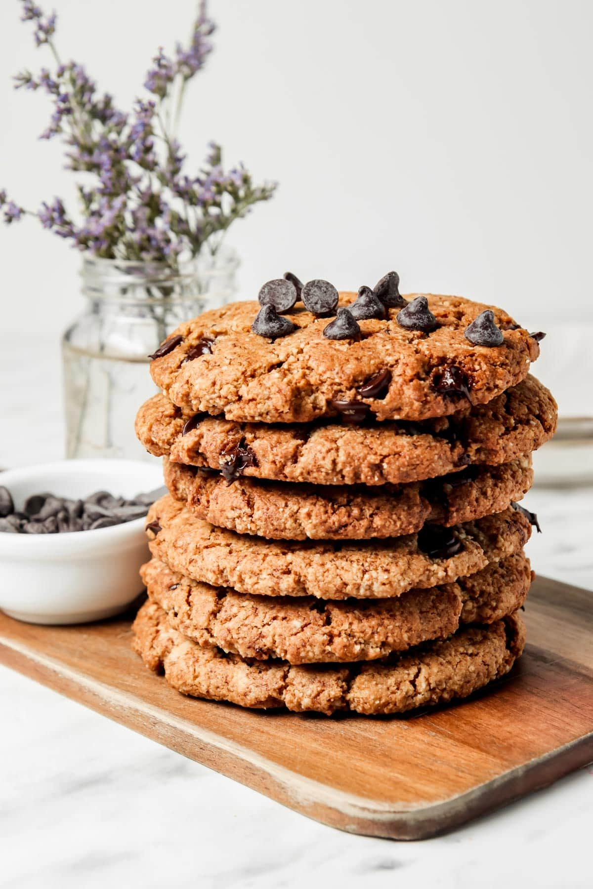 Stack of Almond Flour Cookies, chocolate chips in bowl, flower vase in background