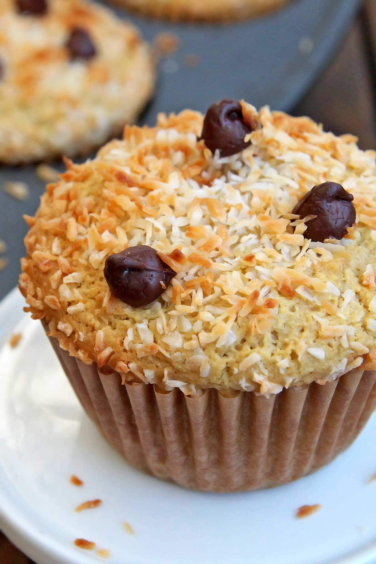 Closeup of coconut almond muffin on tiny white stand