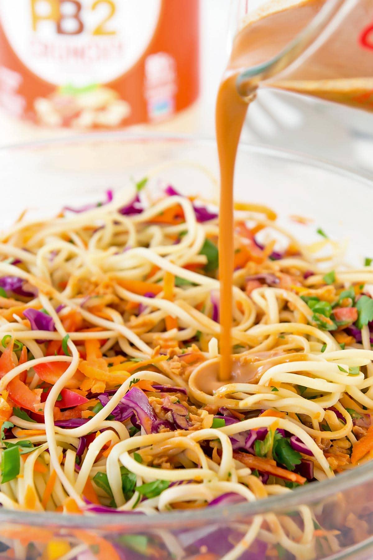Thai peanut noodle salad dressing being poured on