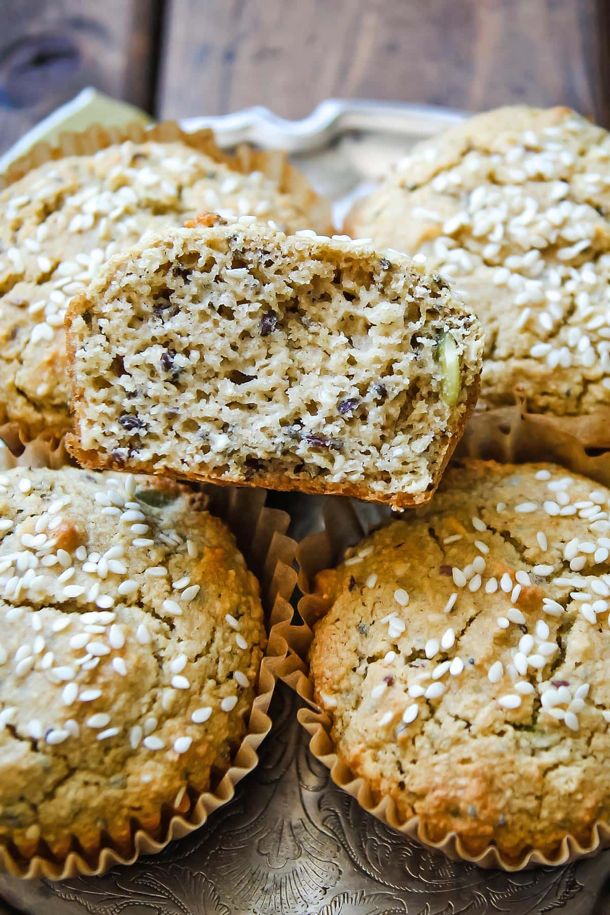 Gluten free tahini muffin half exposing airy texture with seeds for contrast on a stack of whole muffins
