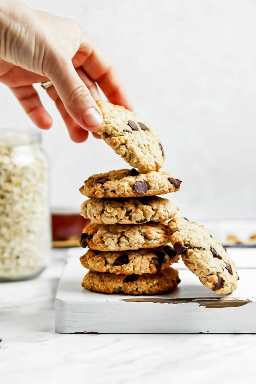 Hand taking a gluten free vegan oatmeal cookie from a stack
