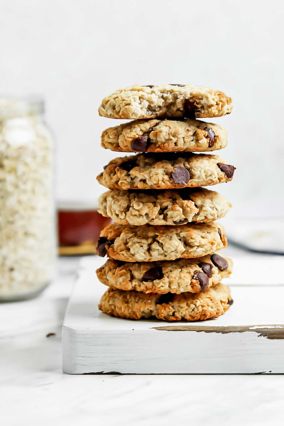 Healthy oatmeal cookie stack on white cutting board