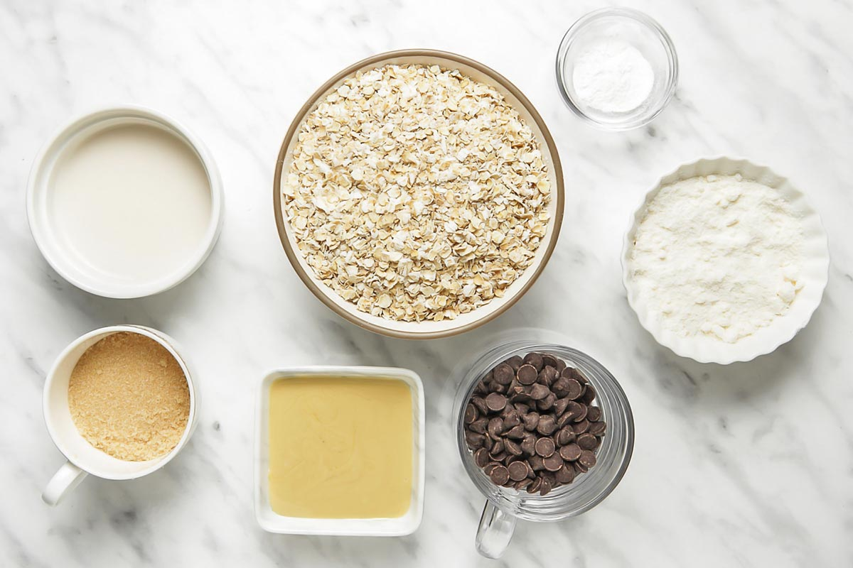 Ingredients for coconut flour cookies with oats laid out in small bowls