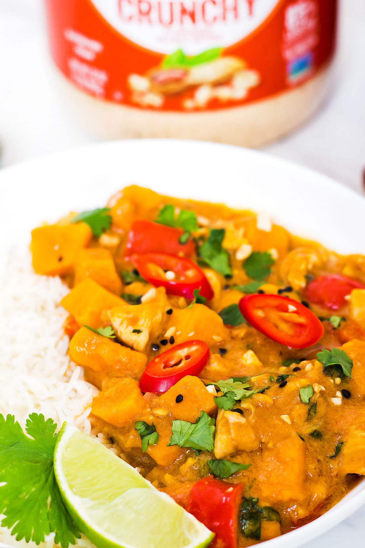 Thai Peanut Curry served with rice, cilantro, and lime wedge