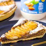 Pear Bakewell Tart slice on black plate with golden fork