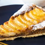 Closeup up of plated pear frangipane tart piece with sliced pears on top glazed with apricot jam