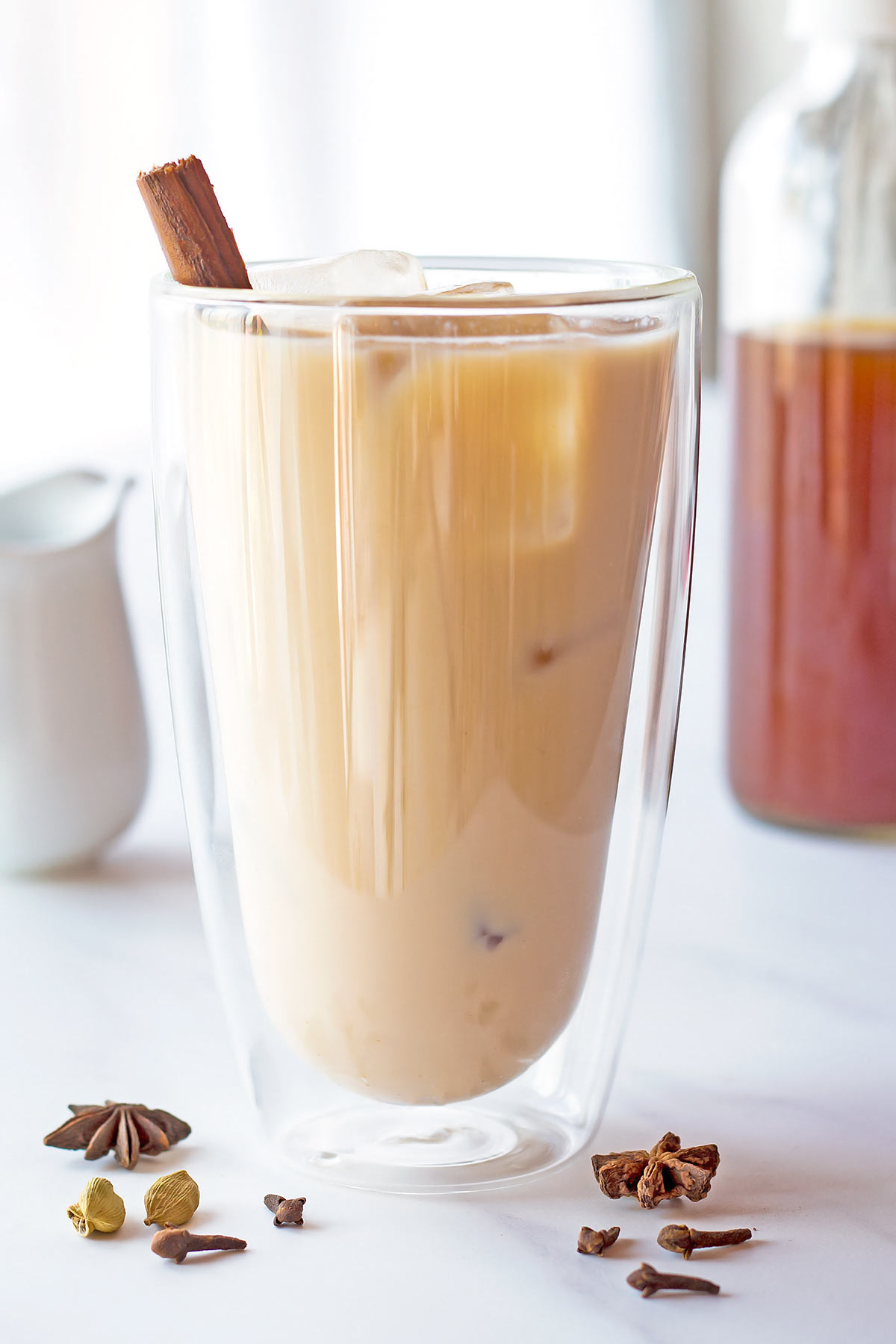 Iced Chai Latte in double-walled glass with bottle of chai concentrate in background
