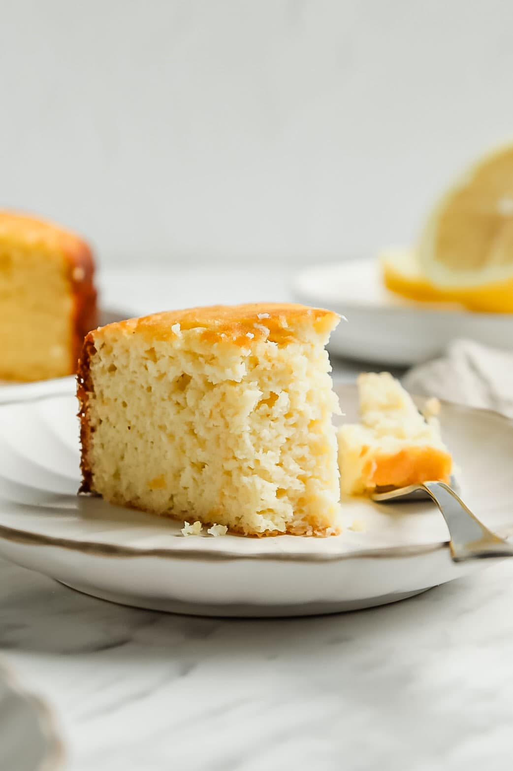 Slice of keto lemon cake with bite taken off with small dessert fork