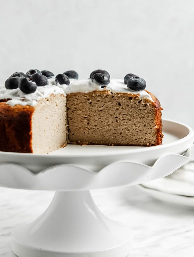 Banana coconut flour cake on cake stand with slice removed to reveal inside view of moist cake texture